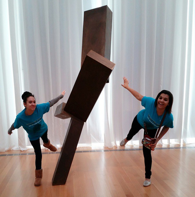 "Kelsey Hunt, left, and Harley Graham, right, students from Fairmont High School in Fairmont, North Carolina, pose with Joel Shapiro's 'Untitled' as part of a virtual exhibit they created during a ""flipped field trip"" at the North Carolina Museum of Art."