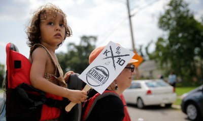 Rizzo Santana, 2, walks with his mother Sierra Santana during a second-line parade to commemorate the 10th anniversary of Hurricane Katrina in the Lower 9th Ward of New Orleans, Saturday, Aug. 29, 2015.