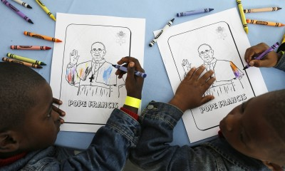 Kaydn Dorsey, 4, left, and Lionel Perkins, 4, draw on a coloring sheet bearing the image of Pope Francis as they wait for him to arrive on a visit to Catholic Charities of the Archdiocese of Washington, Thursday, Sept. 24, 2015. The charity serves dinner to about 300 homeless people daily at the site, and it will serve a meal during the pope's visit.