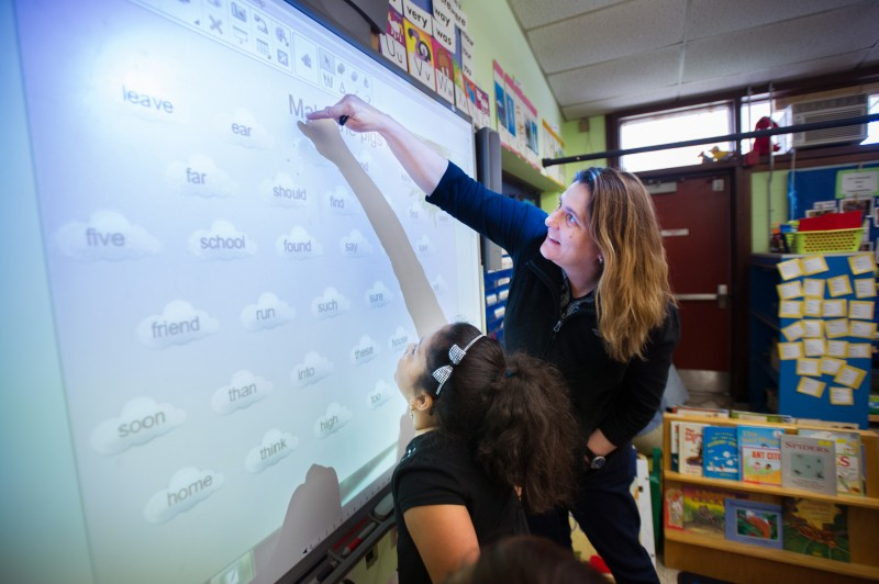 Pleasant View Elementary School Principal Gara Field works with first grader Rachael Rodriguez on a word game on an interactive screen during free time in Rodriguez' class this past May.