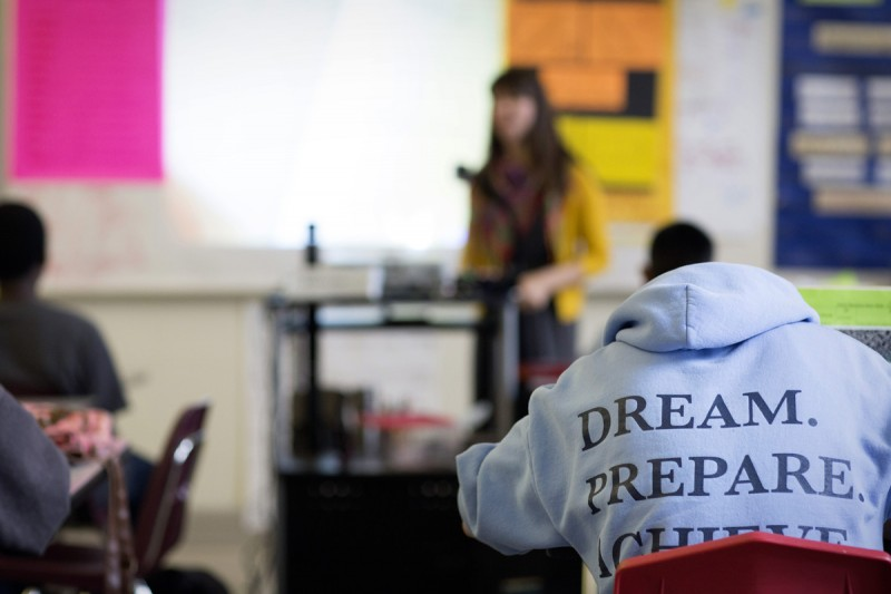 "A student wearing the school sweatshirt — which are sometimes provided to students for free or as an award — concentrates during a math class last spring. ""I was really struck by how deeply poverty has impacted this community in a way that was not true in the other schools [I've worked at],"" said exiting literacy coach Sarah Altschul of Deep East Oakland, where Elmhurst is located."