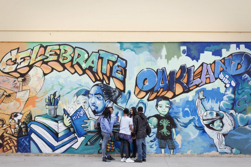 "Students hang out under one of the many murals on the Elmhurst Community Prep campus during a mid-morning break last spring. ""I'm excited about the potential at Elmhurst,"" said Oakland schools' superintendent, Antwan Wilson. ""The talent and the ability is in the building to deliver a great education."""