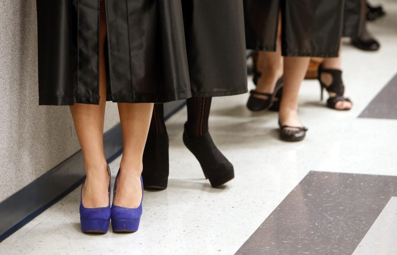Graduates line a hallway waiting for fall commencement at Shelton State community college in Tuscaloosa, Ala.