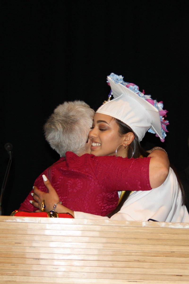 Headmaster Dania Vázquez hugs 2017 graduate Claudette Bautista during the Margarita Muñiz Academy's second graduation ceremony.