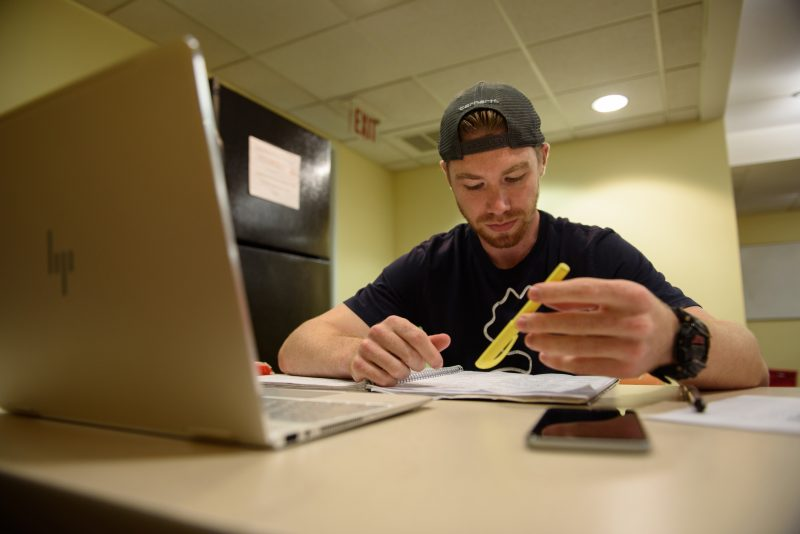 "Josh Caouette, a graduate student at Simmons College, crams for a test. Caouette is resigned to the cost of his degree. ""If it's helping others, that's fine by me. I mean, I have to do it either way."""