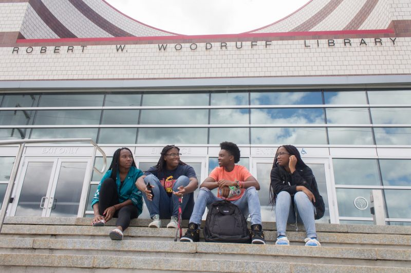 Clark Atlanta University students Destiny Rudolph, Delaina Mims, Charles Finch and Jewel Cannon meet on the steps of the Joseph W. Woodruff Library, which is shared among four Atlanta colleges and universities. Higher-education institutions increasingly are pooling their resources to cut costs.