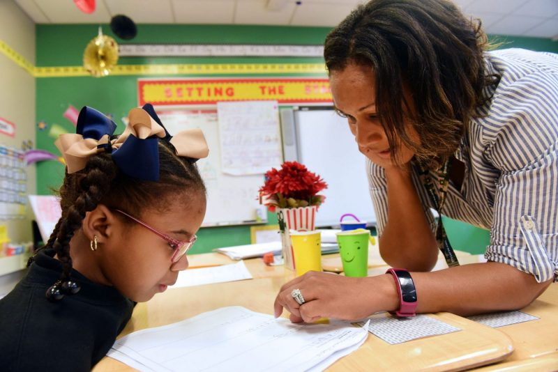 Second grade teacher Lynnon Carney helps a student with math at Arise Academy.