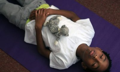 Using a stuffed animal to assist with breathing techniques, fifth-grader Vermetrice relaxes during a yoga class.
