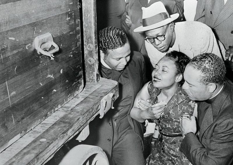Sinking to knees, Mrs Mamie Bradley weeps as body of slain son, Emmett Louis Till, 14 arrives at Chicago Rail Station.