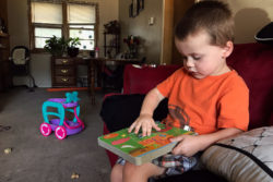 Coltin McNitt, age 2 in this photo, sits on his couch with a book at his home in Wichita, Kan. Colton has been on the waitlist for the local Head Start program, which only has enough funding to serve 6 percent of eligible children nationally. Lillian Mongeau/The Hechinger Report