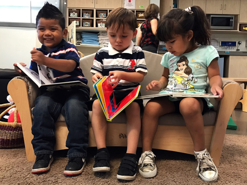 "Educare Arizona classmates Nathan Jaramillo, far left, Esteban Cuevas and Melissa Gordillo ""read"" books during free time in their toddler classroom. Children begin learning basic literacy skills, like which direction to turn the pages, around age 2. Lillian Mongeau/The Hechinger Report"