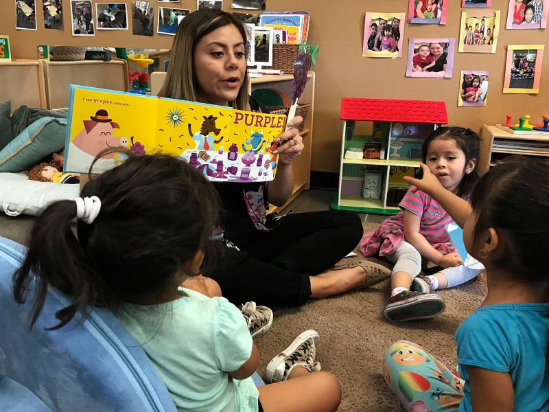 Angelina Salgado, a toddler room teacher, reads a book about colors aloud in the toddler room at the Phoenix, Ariz., branch of a model program for young children called Educare. Most state child care regulations do not require educational activities like reading aloud.