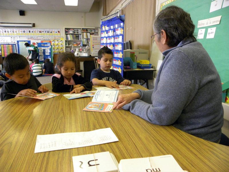 Modesto, California — Afternoon kindergarten teacher Margaret Peralez helps, from left, Cesar Mackan, Monserrat Mendoza and Cristian Bustamante with Spanish reading while morning class teacher Maria Mota leads intensive English vocabulary instruction in the background.