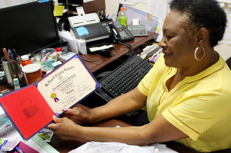 Virginia Dickerson proudly shows off her high school diploma. Grandparents and great-grandparents like Dickerson are still raising school-age children long after their own children finished or dropped out of school.