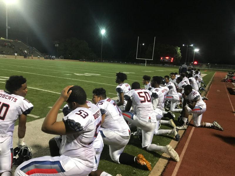 KIPP players kneel while medics help an injured KIPP player.