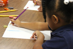 A preschool student writes in class.