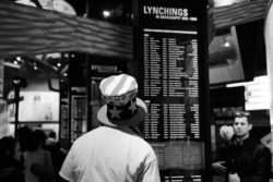 Along with demonstrators, supporters of President Donald J. Trump showed up for the opening day of the new civil rights museum; one supporter looks at a list of those who were lynched.