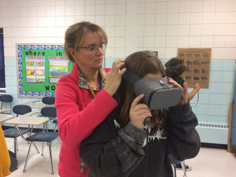 Cornell School District science teacher Susan Dunning helps eighth-grader Madison Litzinger adjust the virtual reality headset.