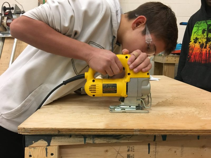 "Freshman Blake Simino-Smith, 14, uses a hand saw to cut a wooden board for a set of stairs during Ritenour High School's new ""Geometry in Construction"" class."