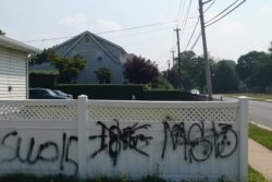 Gang graffiti on a fence in suburban Long Island.