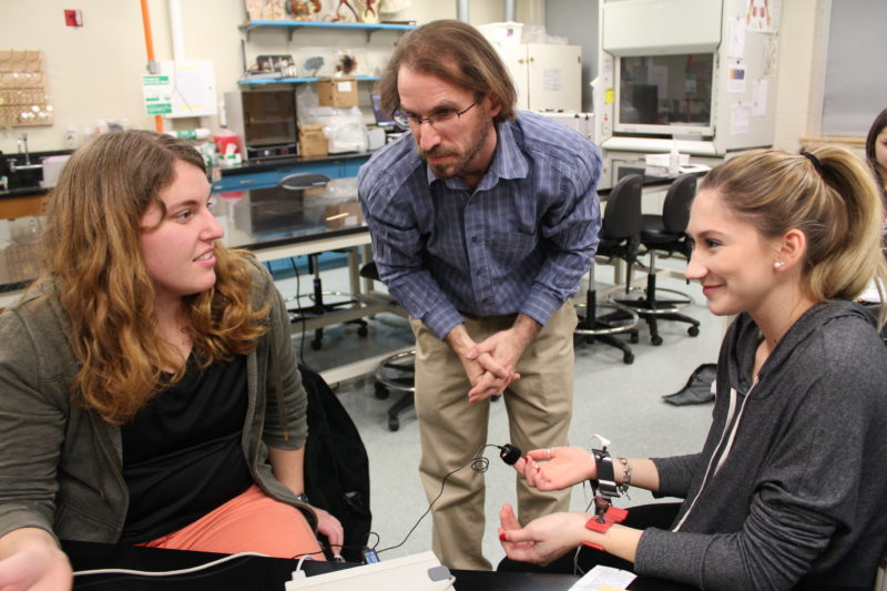 Professor Scott Dobrin works with two students inside a lab at the University of Maine at Presque Isle. Dobrin has embraced the school's new proficiency-based education model and now offers his students many choices inside his classes.