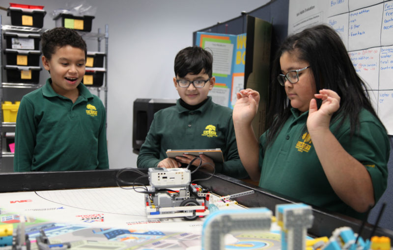 Fifth-graders (from left) Jayden Vargas, David Bojorque, and Ariyana Denny figure out how to make their Lego robot move in a robotics class at Elm City College Prep, in New Haven, Connecticut.
