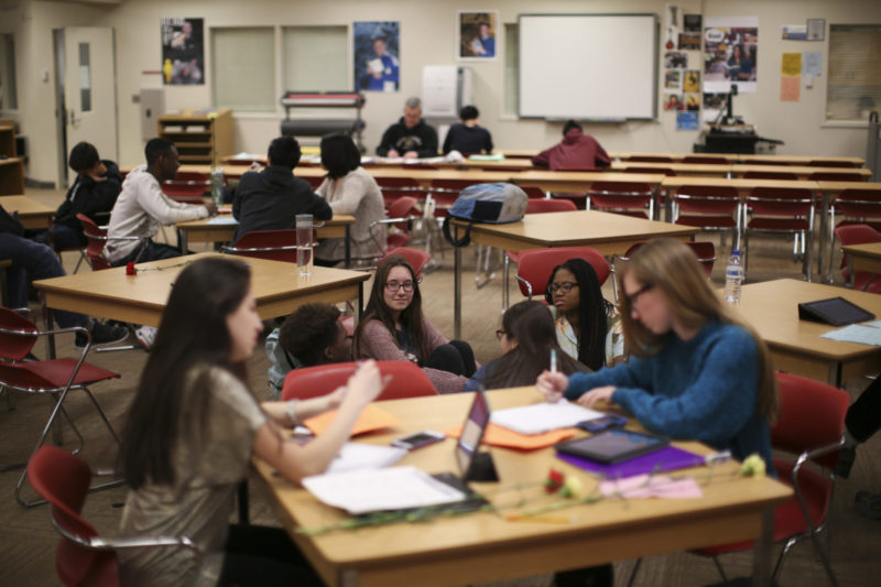 High school students read together in the library.