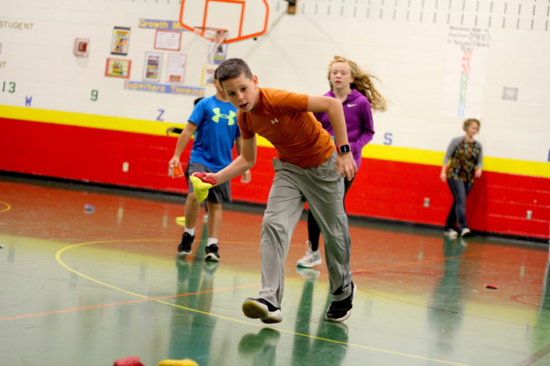 A student throws a bean bag during an early morning game at Horizons Elementary School. Students say participating in morning exercise helps them focus for the day.