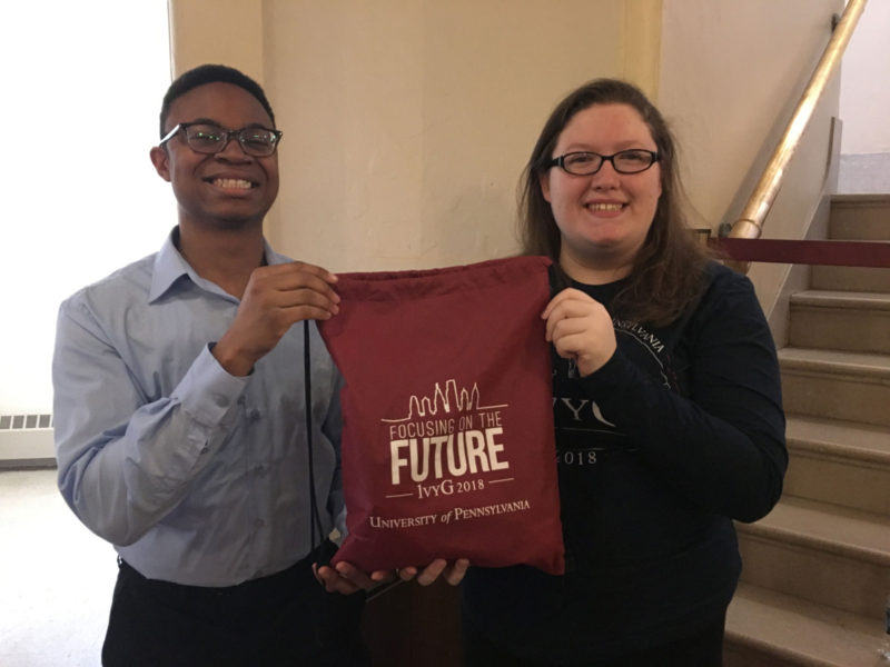 """Alfred """"Red"""" Joseph, a senior history and philosophy major, and Lyndsi Burcham, a junior psychology major, stand outside Irvine Auditorium before the opening ceremony of the fourth annual 1vyG Conference at Penn, holding the SWAG given to attendees bearing theme """"Focusing on the Future."""""""