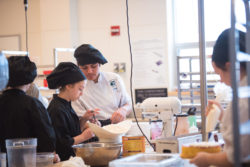 Student Jeremy Pichardo works with freshman Angela Cutone in the Culinary Arts department.