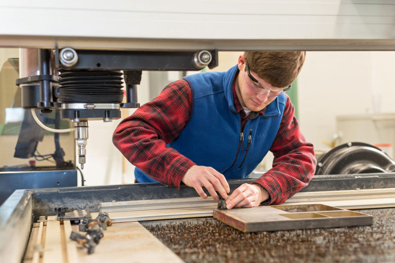 Wes McEntee works on one of several manufacturing machines students use at Vermont Technical College.