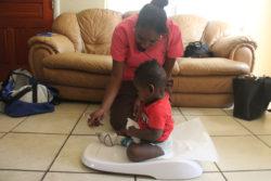 Nurse Polita Williams weighs 8-month-old Jamir during a home visit.