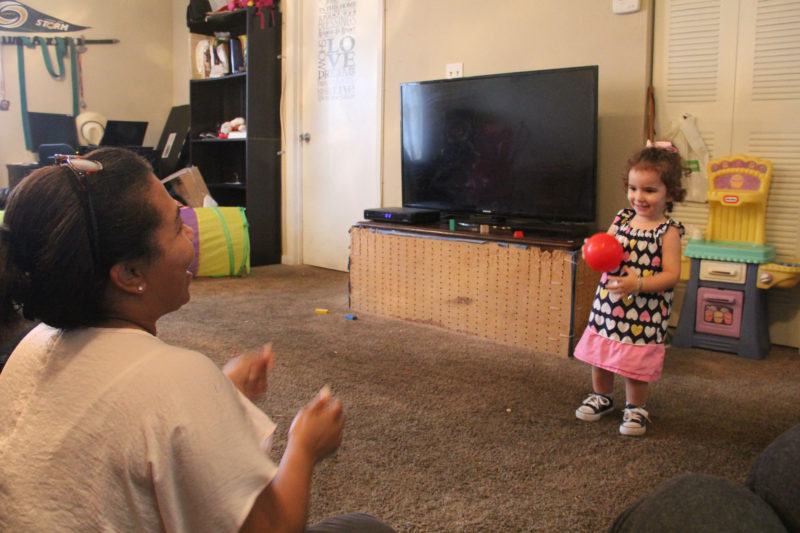 Home visitor Mercedes Castillo throws a ball to 2-year-old Sonja Morales during a home visit.