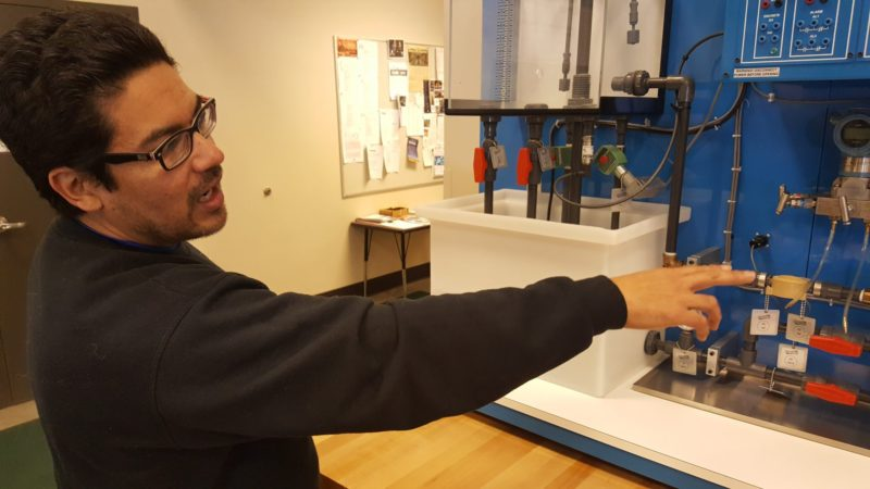Alberto Bellina, who teaches petroleum technology at Williston State College in North Dakota, explains the training equipment in the campus petroleum technology laboratory.