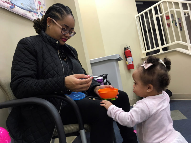 Nikka Norman, a nursing student at the University of Louisville, helps her daughter, Ariyah, with a snack.