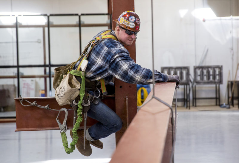 An apprentice ironworker practices attaching I-beams. Ironworkers in this program are already making around $50,000 a year while they train.