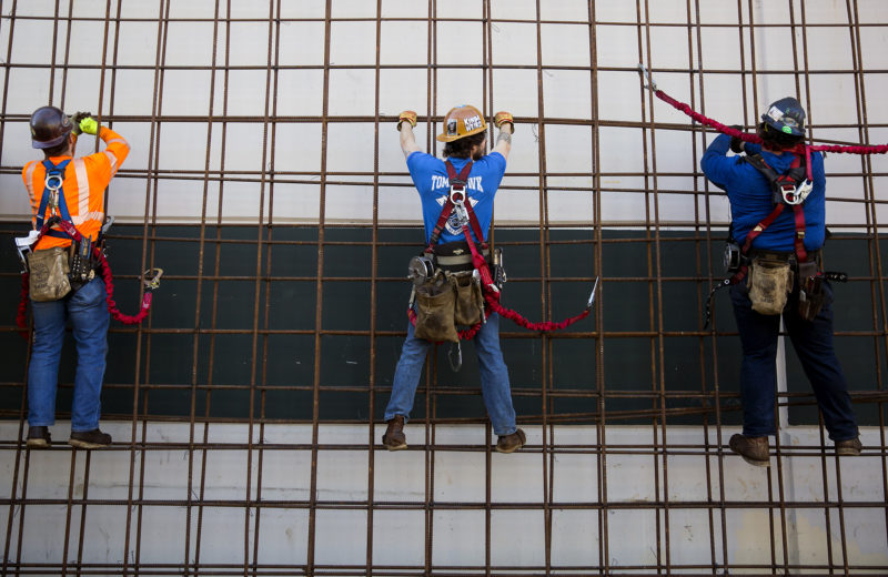 Ironworkers climb rebar on the outside of a training center near Seattle. Ironworkers in this program are already making around $50,000 a year while they train.