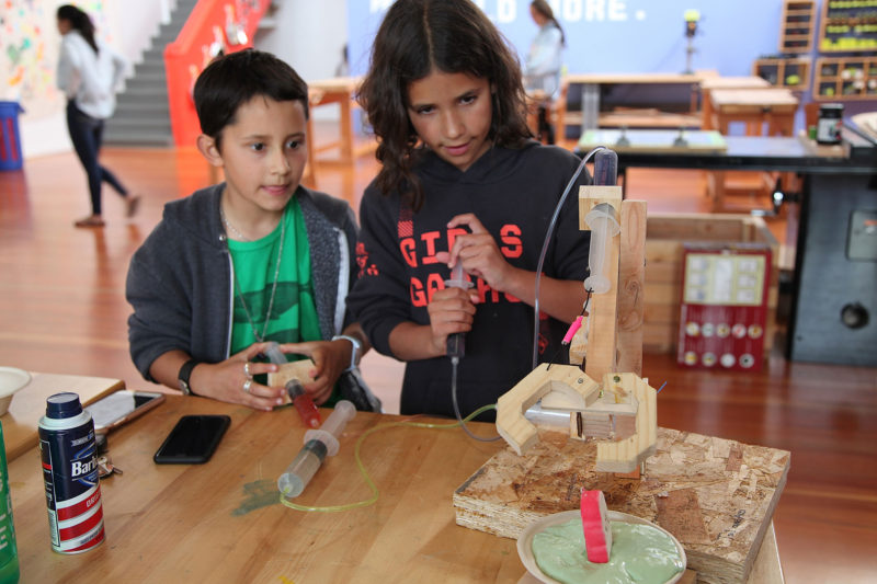 Azi, 9, (left) and Tal, 11, attempt to pull a squishy toy from a bowl of slime using the mechanical claw they constructed at a workshop at Girls Garage, in Berkeley, California.