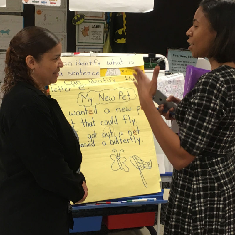 Kindergarten teacher Rosy Taveras, pictured left, receives feedback from reading coach, Xiania Foster.