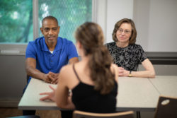 Keith Murphy, recovery counselor, and Lisa Laitman, director of the Alcohol and Other Drug Assistance Program, speaking with a resident of the Rutgers University Recovery House.