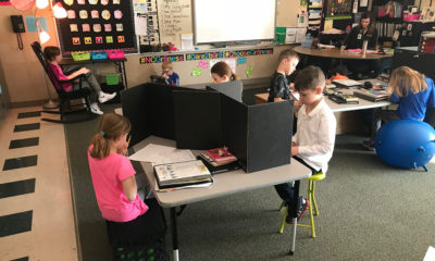 In math teacher Danielle Bosse's classroom, three students take assessments (foreground) while their classmates learn and practice different math skills.