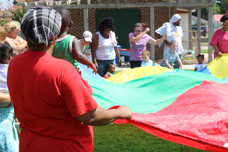 Parents and children enjoy parachute games in Rocky Mount, North Carolina at a June playgroup. Group activities are one way the program, based on the Kaleidoscope Play & Learn curriculum, forms social support networks for parents.