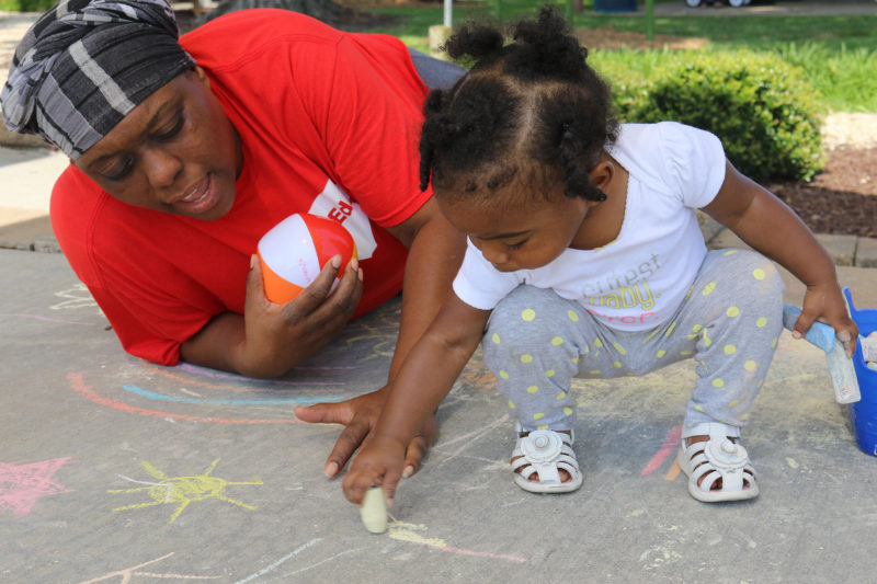 Marletha Muhammad helps her daughter, Khanila, spell her name with chalk at a June playgroup meeting in Rocky Mount, North Carolina The purpose of the meetings is to encourage healthy interactions between parents and their young children.