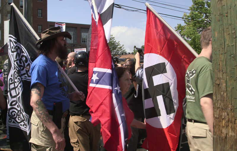 Demonstrators carry confederate and Nazi flags during the Unite the Right free speech rally at Emancipation Park in Charlottesville, Virginia, USA on August 12, 2017.