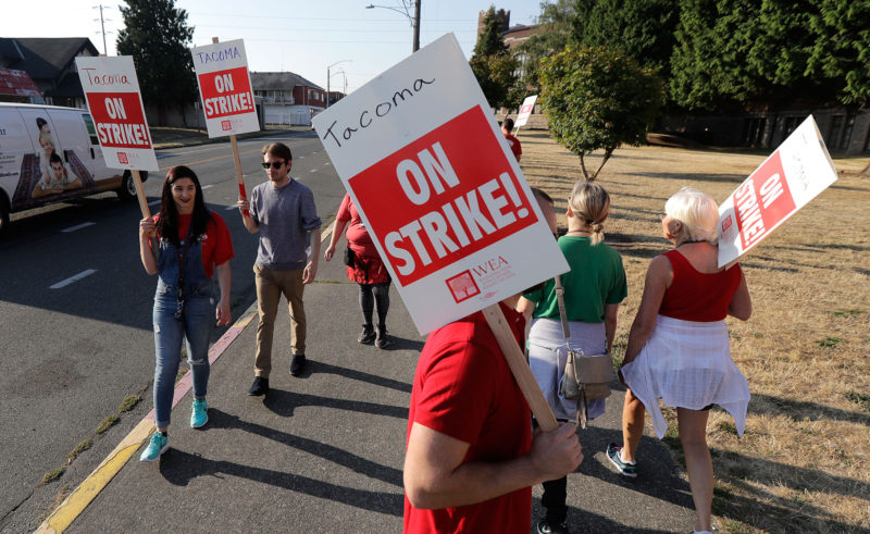 Striking Tacoma Teachers walk a picket line, Thursday, Sept. 6, 2018, in front of Lincoln High School in Tacoma, Wash. Fights over teacher salaries and work conditions are escalating along the West Coast, and the disputes are particularly acute in Washington, a state that has infused at least $1 billion for teacher pay to resolve a long-running court battle.