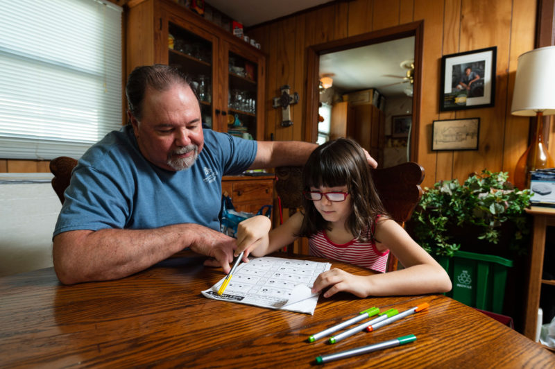 Kevin O'Brien, left, works with Tessa, 7, on her school work.