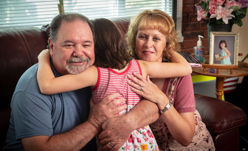 Tessa gives a spontaneous hug to her grandmother, Jodie Hicks, right, and her step-grandfather, Kevin O'Brien.