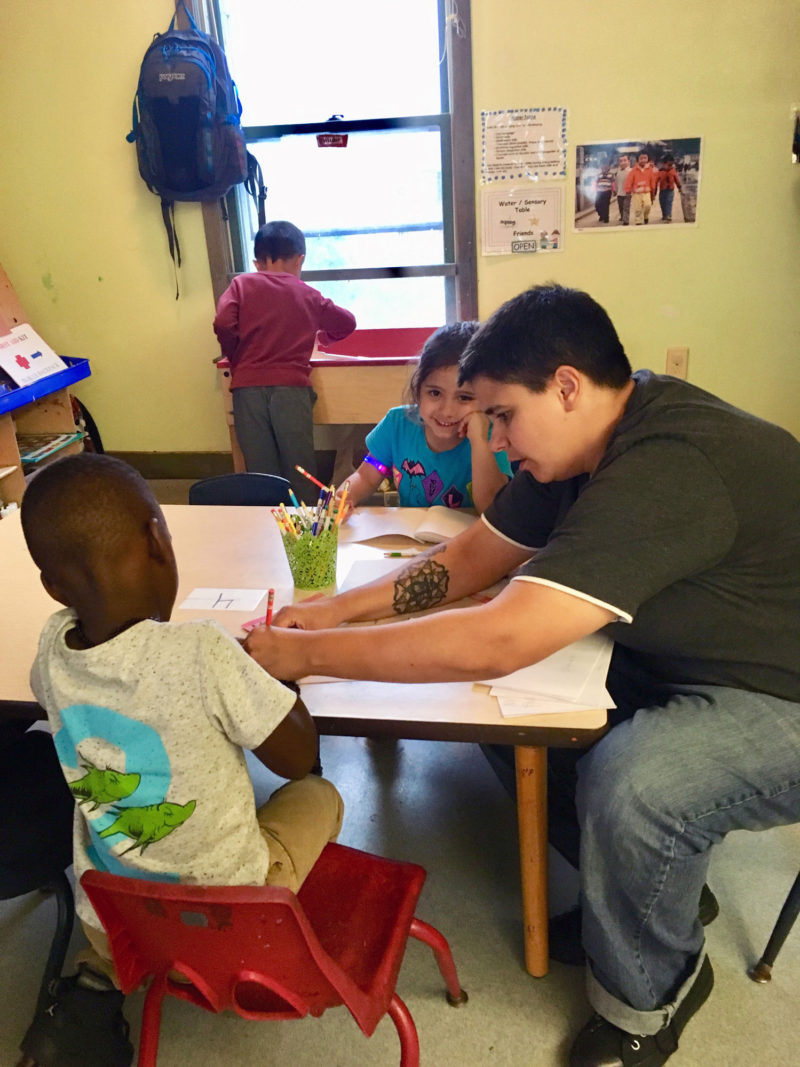 Preschool teacher Kayla Pinto works with a 4-year-old student at the Somerville YMCA in Somerville, Massachusetts. Pinto is working toward a bachelor's degree, with the support of state programs that aim to increase college access for early childhood educators.