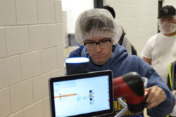 "Matthew Porter, a student at Craig High School, inspects a ""collaborative"" robot at Prent Corporation, in Janesville, Wisconsin."