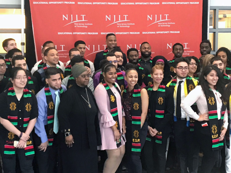 At a pre-graduation program in the spring, happy seniors pose with the program's Associate Director Kim Akhtab while wearing their Educational Opportunity Programs stoles